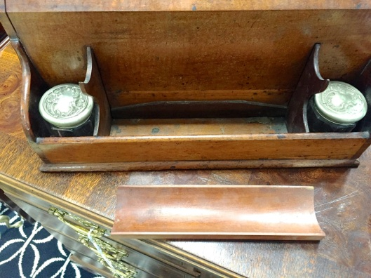No secret compartment unless you count the area under the pen tray, common to most writing desks.