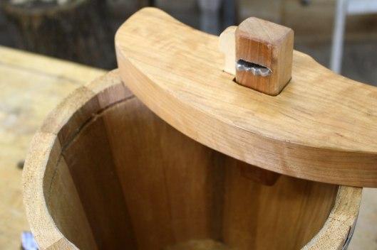 A croze sitting atop a bucket.